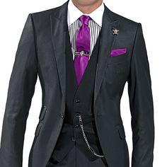 Chaleco de raso negro, corbata con pañuelo fucsia de raso, cadena metálica de bolsillo, pasador, gemelos y colgante solapa con calavera y strass cristal.