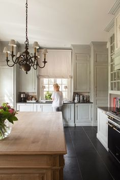 Beautiful kitchen, grey washed cabinets, stone floor, large wood island, antique chandelier, roman shade.