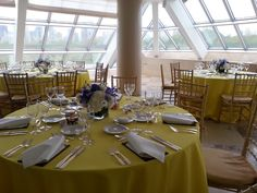 A bright, sunlit interior terrace set with round dining tables draped in bright yellow table cloths, a casual table service and large, elegant purple and white flower arrangments
