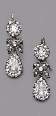 A PAIR OF ANTIQUE DIAMOND EARRINGS  Each designed as an old-cut diamond cluster suspending a diamond-set bow and pear-shaped cluster drop, mounted in silver and gold, circa 1850