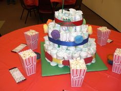 """Carnival/Amusement Park Baby Shower Centerpiece.  Inside are wipes and baby bath products.  Cutouts on ribbon made using cricut.  """"Lollipops"""" on middle tier made using baby washcloths and baby spoons."""