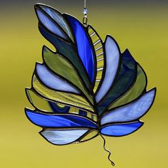 Stained glass blue leaf suncatcher, leaf ornament, leaves, fall decoration, autumn. This beautiful stained glass blue leaf suncatcher is made of hand cut and ground glass in multiple blues and clear. The pieces are individually wrapped in copper foil, and soldered. I then used pewter patina followed by black patina on the solder and stem and buffed to a unique antique finish. The individual colors really pop. It is waxed and buffed to shine. It comes ready to hang with a sturdy hook and…
