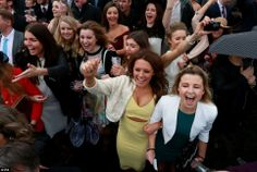 The crowd cheer on the runners in the first race during Grand National Day of the Crabbie'...