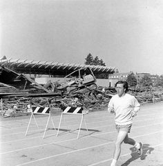 Black and white photo of an unidentified runner jogging in front of the remains of the west grandstand at Hayward Field during 1975 renovation. ©University of Oregon Libraries - Special Collections and University Archives