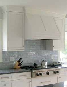 Waterworks Grove Brickworks backsplash tile in Dirty Silver with white cabinetry and honed Absolute Black counters