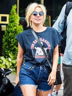 Lady Gaga wears a vintage t-shirt, cutoffs, a black box bag, and round sunglasses