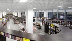 """Livraria da Vila - unidade Shopping JK Iguatemi (SP), de 2011, assinada pelo arquiteto paulistano Isay Weinfeld.  Os 1.700 m² também têm portas-estantes na entrada, mas desta vez o que chama a atenção no projeto da livraria - ao todo são quatro lojas criadas por Weinfeld - é a sinuosidade das paredes e do mobiliário. Uma das inspirações do arquiteto para o """"serpenteio"""", que cria sub-espaços para leitura, são as obras do artista norte-americano Richard Serra"""
