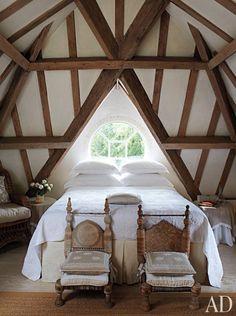 American-oak beams crisscross the ceiling in a top-floor guest room   archdigest.com