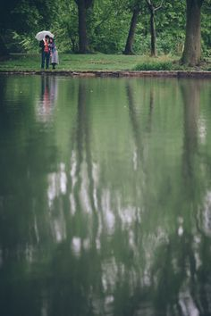 A couple stand by a lake with an umbrella during their rainy engagement session in Prospect Park with NYC wedding photographer Ben Lau.