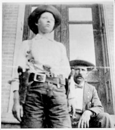 Pearl Hart (c.1871 – after 1928), an outlaw of the American Old West, armed with a .38 revolver. She cut her hair short and dressing in men's clothing.