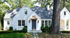 White brick cottage home boasts a dark gray front door flanked by brass carriage wall sconces.