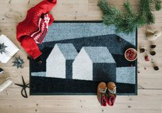 Heim doormat welcomes you home with the motive of a warm and inviting home that lights up in the blue hour, surrounded by Norwegian nature.
