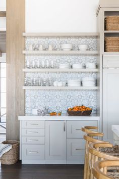 Greige shaker cabinets, modern open shelving, rustic wood accent wall trim, rectangular hardware, patterned ceramic tile feature wall