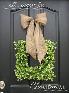 love the simplicity of the large burlap bow over the boxwood wreath on a gray/black door