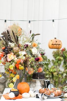 Vintage Halloween decorations with flowers, pumpkins and caramel apples.