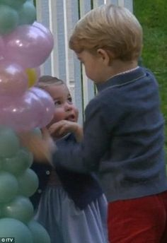Brother and sister play together next to the balloon arch
