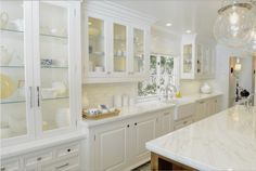 A stunning kitchen, all in white. Our traditional modern design has built in storage throughout. Marble finishes and elegant glass pendant lights.   Custom home by #KellyBaron.