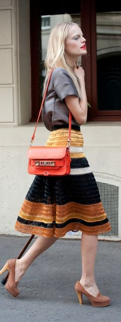 Summer street style inspiration: Not overly complicated, but the textural intrigue on her striped a-line skirt and a pop of cherry-red on her bag, takes this look from casual to covetable.