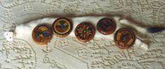 These buttons are made out of Ponderosa Rin and were hand made by a Jemez Indian woman living at Jemez Indian Pueblo, New Mexico.  Designs: 'Rain and Clouds', 'Sun and Moon', 'Trails Crossing and Eagle Feathers', Kachina Dancer' and Thunderbird, bearer of happiness'.