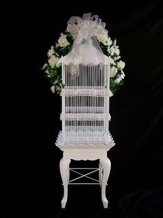Flora decorated Birdcage sitting on small white table! http://www.floridabeachweddingsource.com/images/bird_cage.jpg