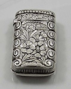 Gorham sterling silver match safe circa 1890 with embossed flowers on both sides and a monogrammed cartouche on one side.