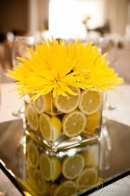Simple lemon centerpieces with blue ribbon - cheap flowers with a lot of impact. The mirror underneath is a really nice idea, maybe at dollar store. With votive candles around it.