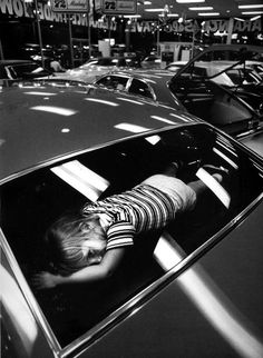 At a new car dealership in 1971 a toddler checks the comfort of the package shelf as a snooze spot for long trips. [736x1005]