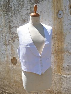 ( N juin)  Antique 1900/1930 a beautiful men tuxedo vest made with textured white cotton called piqué de cotton  . . The back is made with a strong white sateen .The vest is lined with the same sateen . There are 4 motherofpearl seashell buttons at the front . There is a small belt with buckle at the back to adapt the size . 2 pockets . A beautiful  col chale /collar .  Taille : XS/S Lenght : 20.5  ( 52 cm ) at the longest place Schoulder to schoulder : 12.2  ( 31 cm) Bust : 42...