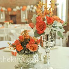 Mokara orchids, garden roses and greenery were placed in mercury glass vases