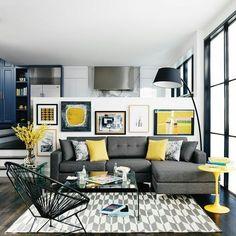 Decoração sala de estar com sofá e almofadas cinza, tapete grafico, almofadas amarelas e quadros.