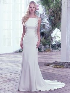 A dramatic scoop back is accented with an illusion closure creating a sexy keyhole below the natural waist. Artfully placed lace embellishments featuring Swarovski crystals adorn each illusion side panel adding a modern twist to this Yolivia Crepe satin sheath wedding dress with high bateau neckline. Finished with a zipper closure.