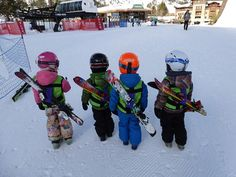 four-children-carrying-their-skis-with-their-Kinderlift-vests