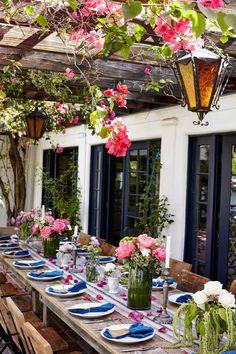 Une table de jardin fleurie installée sous la pergola