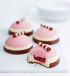 Neapolitan Mousses. Layers of strawberry and vanilla flavoured white chocolate mousse with a strawberry compote centre, dipped in chocolate, decorated with a milk and white chocolate scroll.