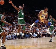 <p>Lakers point guard Magic Johnson tosses a no-look pass past Celtics forward Ed Pinckney during a preseason game. About two weeks later, Johnson announced he was HIV-positive and retiring from basketball.</p>