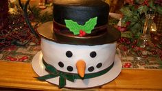 I made this cake for my work christmas party... They loved it>>>>>>>>> frostys head was a white almond cake and the hat was chocolate with peanut butter filling...  all iced in bc.. with fondant accents and ribbons...forgot.. the brim of the hat was to be covered with fondant... ran out...sooooo.. cover a cake board with a black plastic table cloth... worked out well.... TFL