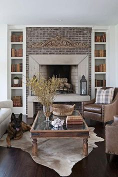 Cottage living room features a brick fireplace with hearth flanked by narrow alcoves filled with bookshelves.
