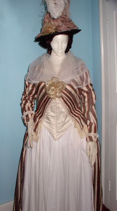 """Pierrot Ensemble c.1780-1790  This outfit has discarded all hoops and uses numerous petticoats over a skirt of white cotton, worn with an open robe of striped brown, russet and cream silk. A long sleeved Pierrot jacket has a white  """"zone"""", front hook and eye closing, and a short basque edged with a cream silk fringe. A black straw hat has a crown of large poufs of coffee brown silk. Feathers rise from a knot of rust ribbon and a black silk band. From diagram XXVI in The Cut of Women's…"""