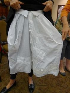 Skirt made from two men's shirts buttoned center front and center back with the collars forming the waistband and the sleeves pushed in to become pockets.