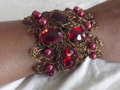 Bracelete em crochê de fios de metal , alumínio esmaltado em ouro velho, bordado com  chaton e pérolas vermelhas.
