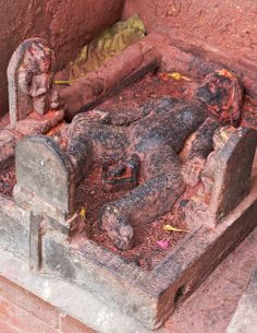 """The unusual and unique Dharti Mata literally translated as Earth Mother at the Bala Bhairav temple complex, Kirtipur, in Kathmandu Valley, Nepal.  The inscription above the reclining figure's head reads """"Dharti Mata"""" in Newari. 19th early 20th century. This image is similar to earth mother idols of south india.  Around her are the 3 figures of Vishnu, Bhrama, Mahadev (Shiva).  The Idol is very important to the temple, and is worshiped as a goddess for fertility. There is likely some deeper…"""