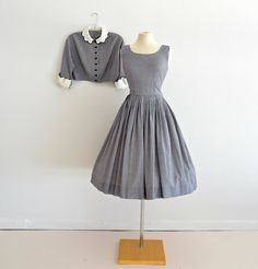 Darling 1950s cotton day dress and jacket. Dress has a fitted sleeveless bodice. Trim waistline. Full knife pleated skirt. Collar cropped jacket has three