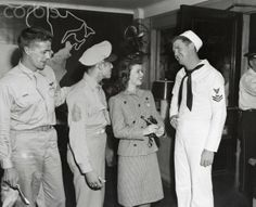 """Original caption: New York: The """"Little Colonel"""" Comes To Town. A much bigger girl than she was when she last visited New York, Shirley Temple breezes into the big town and makes her first port of call the Pennsylvania Station U.S.O. Lounge. Spotted by a couple of eagle-eyed servicemen, she is giving her autograph to the boys."""