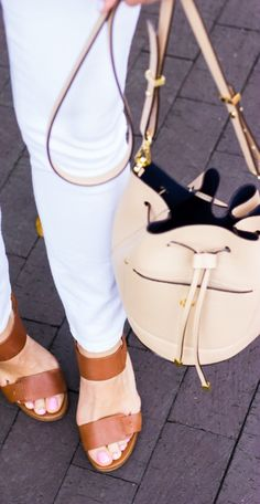 Signs of spring -- pale pink bucket bags, white jeans, sandals. | @anntaylorstyle