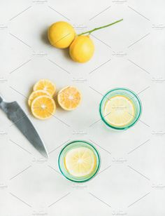 #Morning detox lemon water in glasses  Morning detox lemon water in glasses and fresh lemons over light grey marble background top view selective focus vertical composition. Clean eating weight loss healthy detox dieting concept
