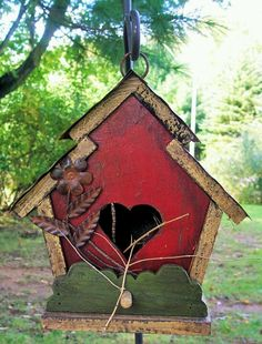 Red birdhouse. Love the heart-shaped opening.