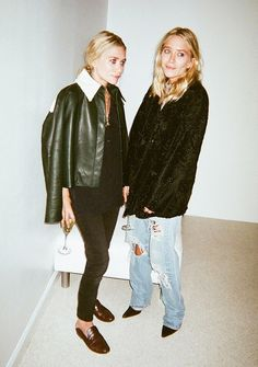 Left, Ashley Olsen wears a black top, skinny jeans, a cropped jacket, and backless loafers. Right, Mary-Kate Olsen wears a black coat with baggy jeans and pointed-toe heels