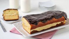 Decadent pastry cream layered between moist yellow cake and topped with chocolate glaze shaped to look like a giant eclair!