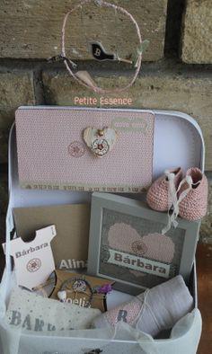 """En esta pequeña maleta podrás encontrar: un cuadro en tela y papel troquelado con tul con el nombre del bebé, una libreta con su inicial para las notas de mamá ..., una """"tarjeta-body"""" de felicitación personalizada, unos patucos, una práctica gasa, un decorativo colgador con su inicial y un pequeño detalle para la mamá: una pulsera elaborada ¡con mucho amor!"""