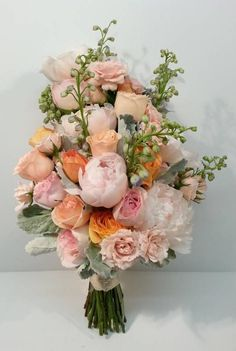 soft pastel peach pink pale blue silver dusty millar sheaf wedding flower bridal bouquet calgary